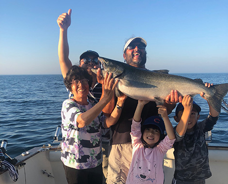 kids holding up a salmon on a fishing charter